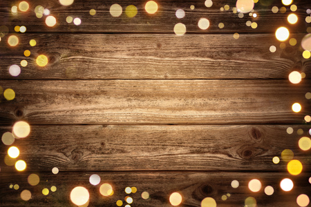 Festive rustic wood background with dark vignette and framed by glowing bokeh lights, ideal for Christmas, advertisement or party