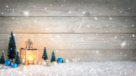 Christmas background with wooden board, falling snow, a burning candle in a lantern and ornaments Archivio Fotografico