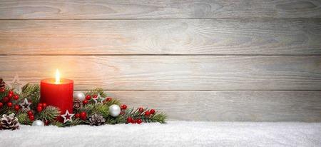 Boże Narodzenie lub Adwent drewna tle z płonącą świecą na śniegu, ozdobione gałęzie jodły i ozdoby, panoramiczny format z miejsca kopiowania Zdjęcie Seryjne