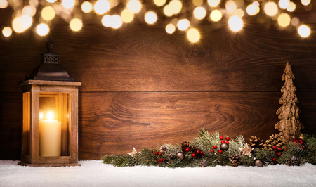 Christmas scene with a lantern, ornaments and blurred lights in front of an illuminated elegant dark wooden board as copy space