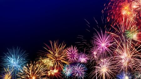 暗い青色の背景は、新年やその他のお祝いのイベントに最適の境界線として色とりどりの花火