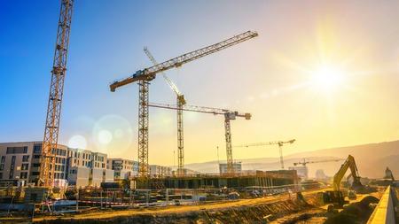 澄んだ青い空と太陽と、複雑な建物に取り組んでいくつかのクレーンを含む大規模な工事現場