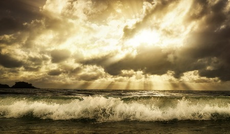 Dramatic cloudscape over the sea with rays of sunlight and a foaming wave in the foreground, toned warm colors