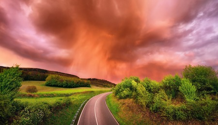 Spectacular rain clouds over a road and green landscape at sunset, with warm red light and dramatic sky