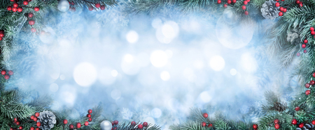 Christmas Background with frosty fir branches as a frame around blue bokeh copy space Imagens