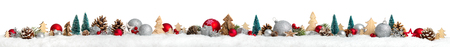 Christmas border or banner with ornaments arranged in a row on snow, extra wide and isolated on white background Stockfoto