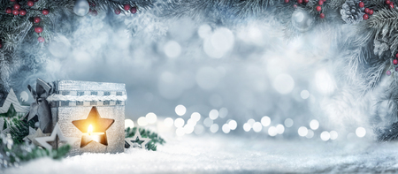 Christmas wide background in silver blue colors with a lantern, fir branches, ornaments and out of focus lights
