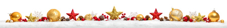 Christmas border or banner with stars and baubles arranged in a row on snow, extra wide and isolated on white background