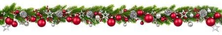 モミの枝、赤と銀のつまらない、マツ円錐形および他の装飾は、白で隔離の吊りガーランドと余分なクリスマス国境