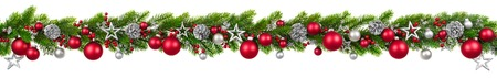 Extra wide Christmas border with hanging garland of fir branches, red and silver baubles, pine cones and other ornaments, isolated on white Standard-Bild