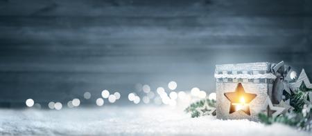 Vánoční pozadí v chladných zimních barvách se svítícím lucernem, dřevěnou deskou, větvemi, ozdobami a zaostřenými světly