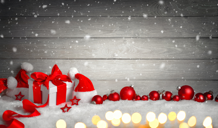 Christmas wood background with a white gift box, red bow and ribbon, baubles, Santa hats, blurred lights and snow