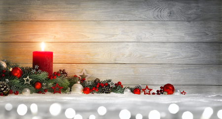 Christmas or Advent wood background with a burning candle on snow, decorated with fir branches, lights and ornaments, panoramic format with copy space Imagens