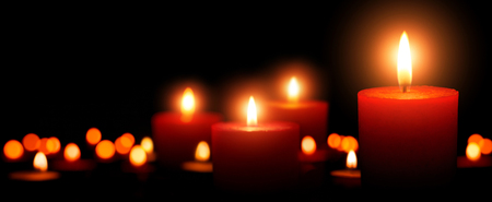 Low-key studio shot of elegant advent candles with four flames in the foreground, black background with defocused flames
