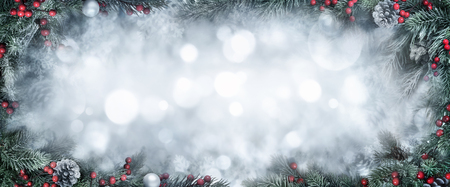 Christmas Background with frosty fir branches as a frame around silver bokeh copy space Imagens