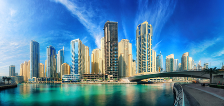 Dubai Marina under the blue sky, with the skyline and clear turquoise water, panorama shot