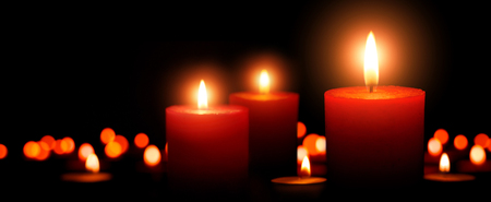 Low-key studio shot of elegant advent candles with three flames in the foreground, black background with defocused flames Imagens