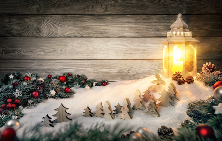 Cozy Christmas arrangement with wooden wall, fir branches and ornaments on snow in the warm candlelight of a beautiful lantern
