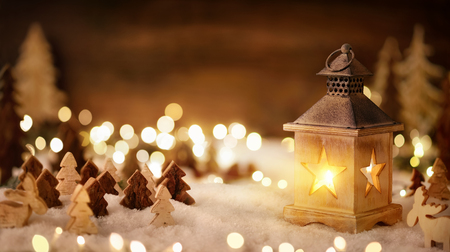 Cozy Christmas arrangement with beautiful wooden ornaments on snow in the warm candlelight of a nice lantern and bokeh lights, low-key studio shot