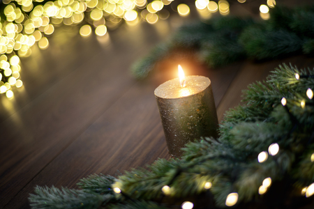 Christmas mood with candle, fir branches and lights on dark wooden table Imagens