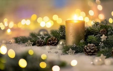 Christmas decoration in warm light with candle, lights, fir branches and ornaments on snow