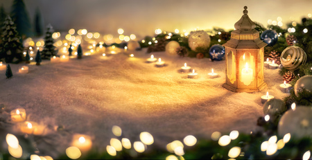 Christmas decoration in warm light with lantern, lights, fir branches and ornaments on snow, panoramic format