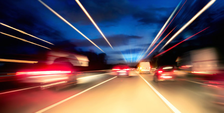 Driving fast on the highway or German Autobahn at night, cars and lights with motion blur