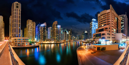 Dubai Marina at night, with the skyline and colorful reflections on the water
