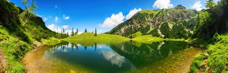 Gorgeous lake surrounded by mountains, with deep blue sunny sky and the amazing scenery reflected in the clear water Archivio Fotografico