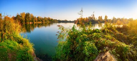 Lake with clear blue water surrounded by trees and vegetation before sunset, panoramic view