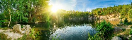Panoramic landscape shot of idyllic lake surrounded by trees and cliffs, with the sun glowing on the horizon Archivio Fotografico