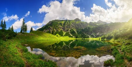 Gorgeous lake surrounded by mountains, with dramatic sunlight and the amazing scenery reflected in the clear water