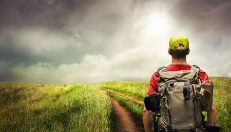 Young man hiking a path leading to the horizon on the open countryside, with dramatic sky and light mood Archivio Fotografico