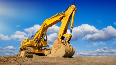 Big excavator on new construction site, in the background the beautiful blue sky with white clouds