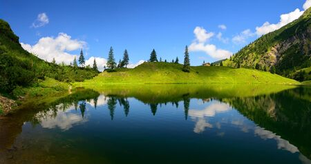 Mountain lake shore in sunlight and shadow symmetrically reflected in the clear blue water creates an almost surreal scenery