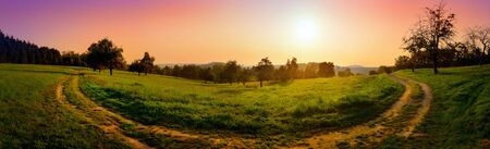 Dreamy and dramatic sunrise over rural landscape: colorful panorama shot of a curved path on a meadow with red and purple sky Archivio Fotografico