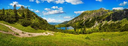 Gorgeous mountain range surrounding a lake, with deep blue sunny sky and green meadows in the foreground