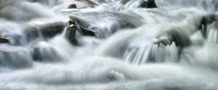 Streams of water beautifully cascading down a wild small river, panoramic format and long exposure for abstract flow