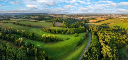 Gorgeous aerial landscape panorama after sunrise: European meadows and forests with blue sky and leading lines Archivio Fotografico