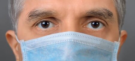 Studio closeup shot of middle-aged man with protective face mask in the corona crisis, looking straight into the camera