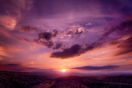 Dramatic, emotional and romantic sunset sky in dark gorgeous red and purple colors