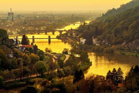 Heidelberg and the Neckar river, Germany, at a gold sunset, shot from above with a yellow filter to enhance the beautiful romantic mood