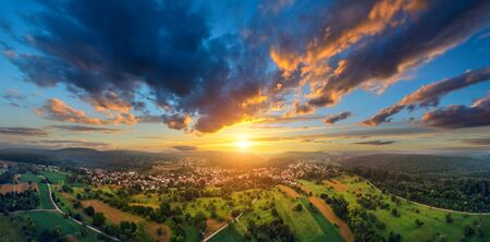Aerial panorama of a vast landscape with a small town at a gorgeous colorful sunset with dramatic sky