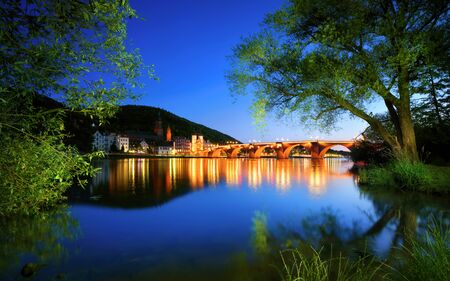 Neckar river in Heidelberg, Germany, at dusk, with deep blue sky reflected in the clear water and green trees framing the illuminated Old Bridge Archivio Fotografico