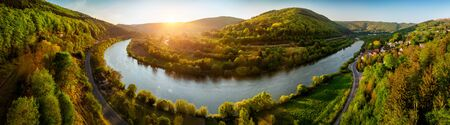 Panoramic aerial landscape shot of Neckar river, Germany, at a beautiful sunset, with clear sky and the vegetation being colorfully lit, a road following alongside the water Archivio Fotografico