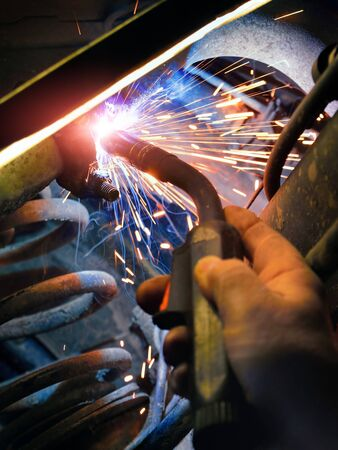 Welding work at a car service station: closeup of a mechanic's hand repairing metal parts with a welder, colorful shot