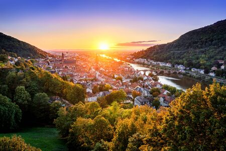 Travel shot: aerial view of Heidelberg, Germany, in beautiful sunset light, framed by colorful trees and gold and purple clear sky, with the Neckar river leading to the sun Archivio Fotografico