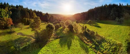Aerial landscape panorama after sunrise: gorgeous scenery with the sun in the blue sky, trees on green meadows casting long shadows, surrounded by forests on hills Archivio Fotografico