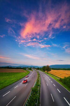 Route large et presque vide sous le ciel coloré après le coucher du soleil, avec de beaux nuages rouges et deux voitures rouges avec un léger flou de mouvement, un transport dynamique et une photo de paysage