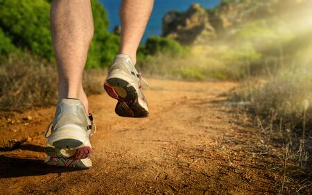 Running outdoors in the mountains by the sea, a dynamic closeup of the male runner's feet on the dirt road lit by the warm rays of light